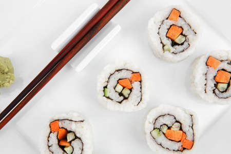 Japanese Cuisine - California Maki Roll made of Smoked Salmon, Cream Cheese and Deep Fried Vegetables inside. With wasabi . isolated over white background on square plate photo