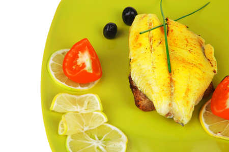 savory: fish fillet with tomatoes,chives and lemon on plate photo