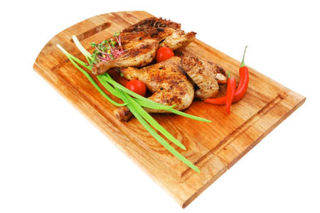 roast meat : chicken legs garnished with green sprouts and peppers on wooden plate isolated over white background photo