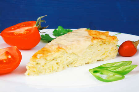 food : vegetable casserole piece over white plate served with parsley and tomatoes on blue table photo