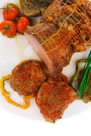ready to cook food: meat with chives and tomatoes over white plate