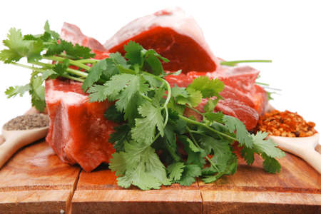 fresh meat : raw uncooked fat lamb pork rib and fillet with green stuff and red chili pepper on wooden plate isolated over white background photo