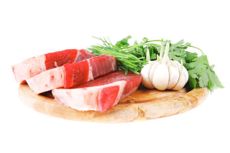 circular muscle: fresh meat : raw uncooked fat lamb pork fillet with green stuff and garlic on wooden plate isolated over white background Stock Photo