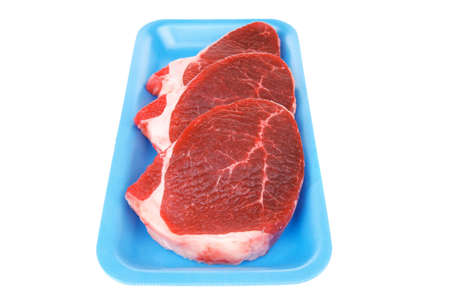 circular muscle: uncooked meat : raw fresh beef pork tenderloin strip ready to cooking on blue tray isolated over white background