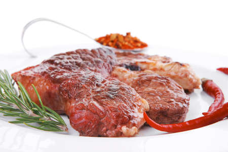 meat food : roasted steak on white plate with red thin chili pepper and spices isolated over white background photo