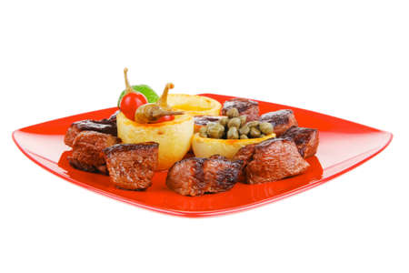 european food: roast beef meat over red plate isolated on white background with hot peppers, capers , olives oil , and bbq sauce photo