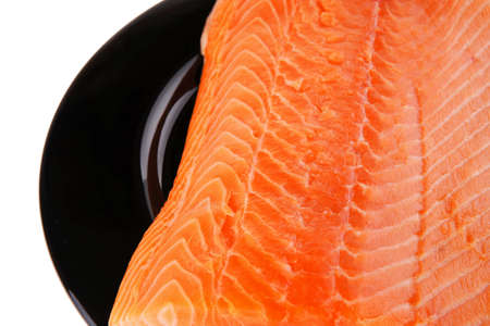 piece of salmon fillet on black plate over white photo
