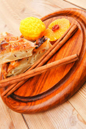 golden section: baked food: apple pie on wooden table served with lemon and cinnamon sticks