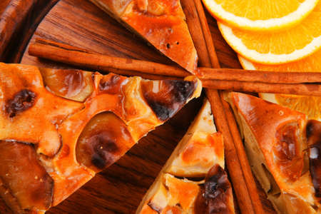 golden section: sweet food : apple pie cuts served on wooden plate over table with cinnamon and lemon