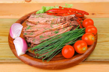 hot beef on wooden plate over wood tables photo