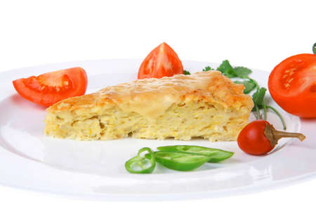 meatless: food : cheese casserole piece over white plate served with peppers and tomatoes isolated over white background