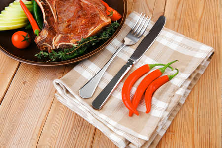 savory : grilled spare rib on dark dish with thyme pepper and tomato on wooden table photo