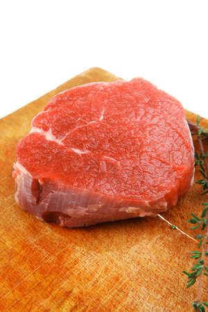 dry sausage: red fresh fillet chops : raw beef fillet on wooden board with thyme ready to prepare . isolated over white background Stock Photo