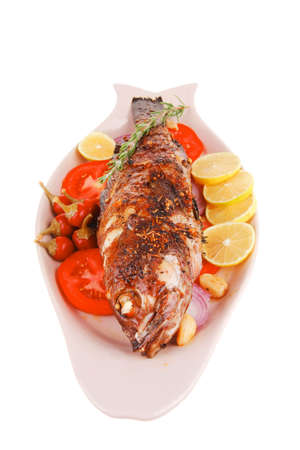 sunfish: whole fried bass on plate, served with lemons and tomatoes