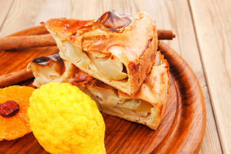 golden section: sweet apple cake on wooden table with lemon and cinnamon sticks Stock Photo