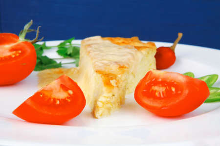 meatless: food : cheese casserole piece over white plate served with peppers and tomatoes on blue table