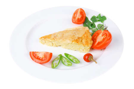 food : vegetable casserole triangle on white plate with pepper and tomatoes isolated over white background photo