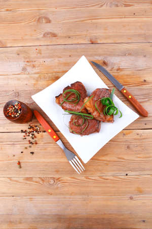 baby cutlery: grilled meat beef steaks strips on white plate with pepper and cutlery over wood table
