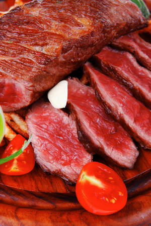 roast steak on potato : fresh grilled beef meat on wood plate with pepper and tomato isolated on white background photo