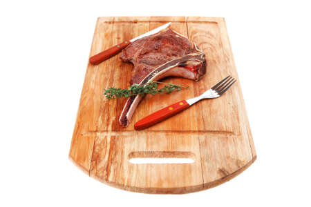 meat food : roast rib on wooden plate with thyme isolated over white background photo