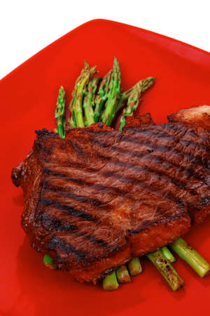 meat table : rare medium roast beef fillet asparagus served on red dish isolated over white photo