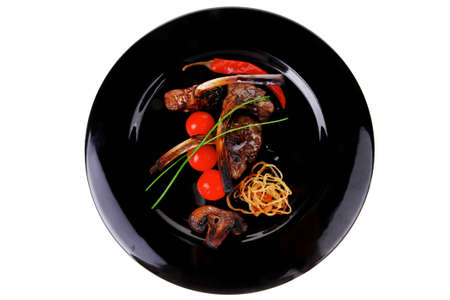 grilled ribs on black plate with vegetables photo