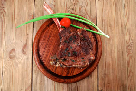 boned: served main course: boned roasted lamb ribs served with green chives and cherry tomato on wooden plate
