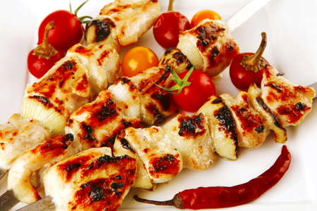 fresh grilled chicken shish kebab on white platter photo