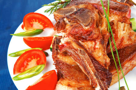 fresh roasted lamb meat fillet ready on china plate with tomatoes, green pepper , and garlic over blue wood table photo