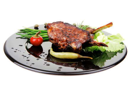 entree: meat savory: roast ribs on black plate with peppers and chives Stock Photo