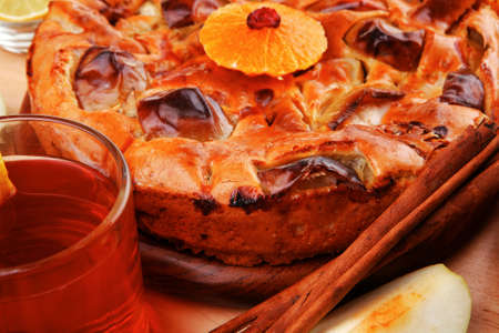 baked food: round apple pie on wooden plate served with fresh lemon, mandarin, and cinnamon sticks on table photo