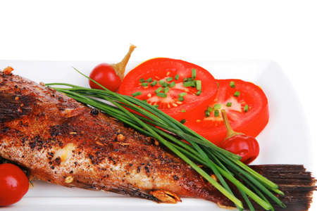 savory isolated on white: whole fryed sunfish over plate with tomatoes lemons and peppers photo