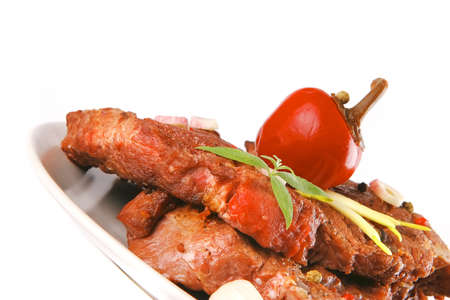 beef chunk served on dish with red pepper photo
