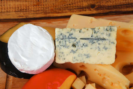 image of cheeses on wooden plate over table photo
