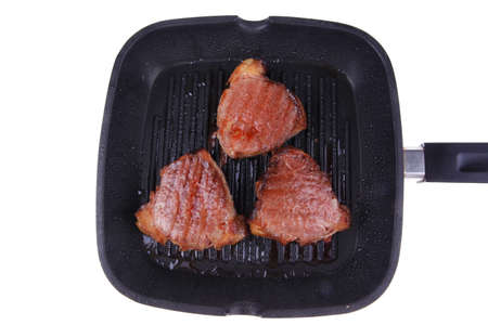 roast bloody beef fillet steaks on black teflon grill plate isolated on white background photo