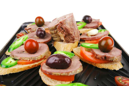 snakes on black grill plate : tartlets with sliced meat isolated over white background Stock Photo - 21603872