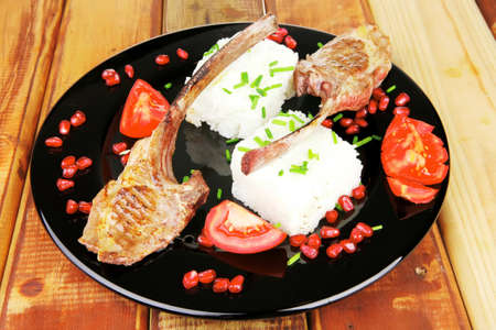 meat food: ribs on black with rice garnich and tomatoes on black on wood photo