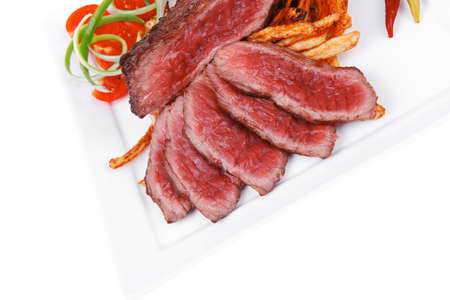 meat food : rare beef on potato chips with pepper and tomatoes over plate isolated on white background photo