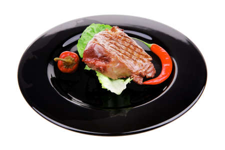 bbq : beef (pork) steak garnished with green lettuce and red chili hot pepper on black dish isolated over white background photo