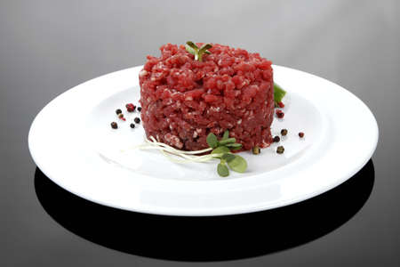 very big raw hamburger cutlet with sprouts and chilli pepper on white plate over black background Stock Photo