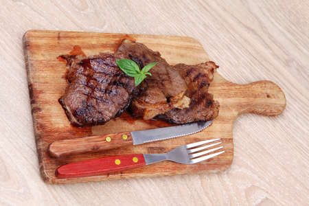 bbq beef meat fillet on wooden plate with cutlery photo