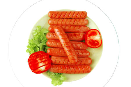 grilled sausages served on green dish wtih tomato photo