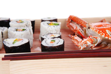 Maki Roll with Deep Fried Vegetables inside . on wooden plate with live crab . isolated over white background . Japanese Cuisine photo
