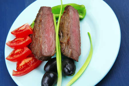 meat savory : grilled beef fillet mignon on blue plate with pepper chives and black greek olives over blue wooden table photo