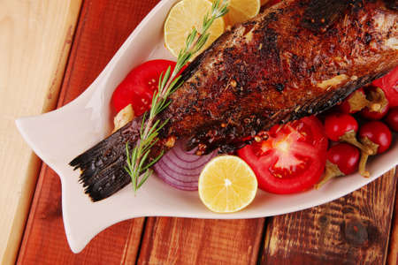 sunfish: savory: whole fryed sunfish over wood with tomatoes lemons and peppers Stock Photo