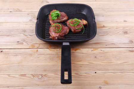 grilled beef fillet strips on grill teflon black plate over wood photo