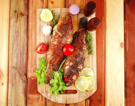 main portion of two grilled fish served on wooden table with castors photo