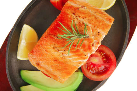 food: grilled salmon on iron pan over wooden plate isolated on white background photo