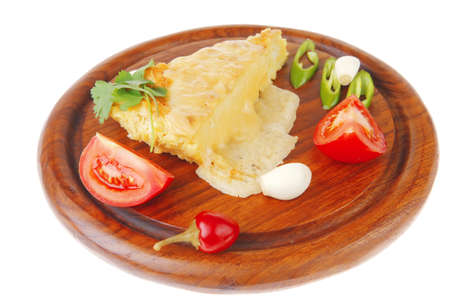 dairy food : cheese casserole piece over wood plate served with peppers , tomatoes and chives isolated over white background photo