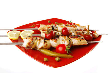 chicken shish kebab on red platter with vegetables photo